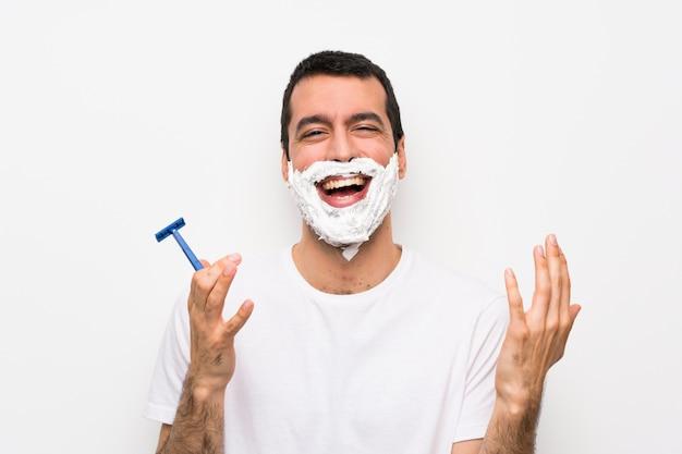 Hombre afeitándose la barba sobre una pared blanca aislada sonriendo mucho