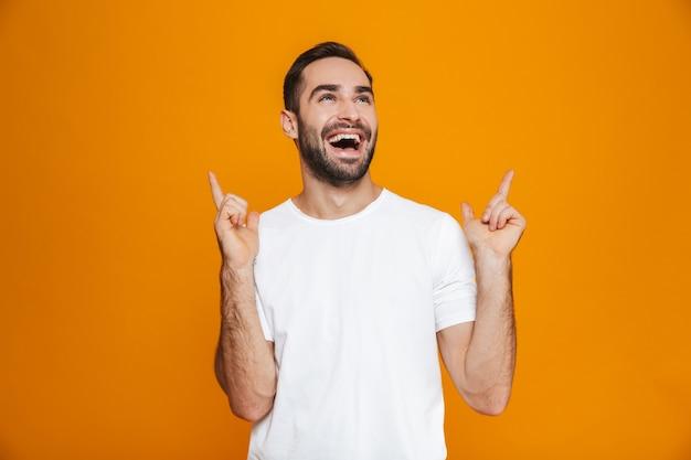 Hombre sin afeitar en camiseta apuntando con el dedo hacia arriba mientras está de pie, aislado en amarillo