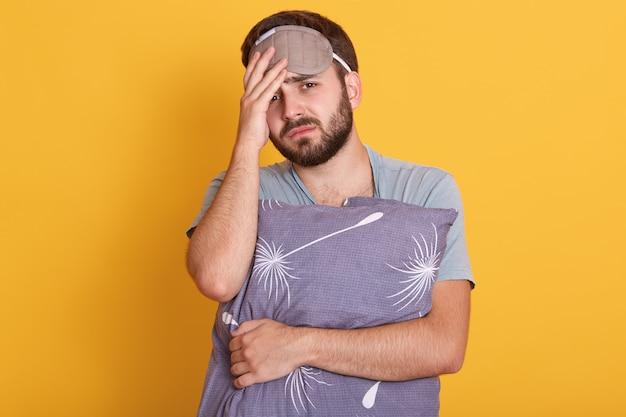 Hombre sin afeitar cansado de pie contra la pared amarilla, sosteniendo una almohada gris, tocándose la cabeza, vistiendo una camiseta gris y una venda en los ojos, se siente mal