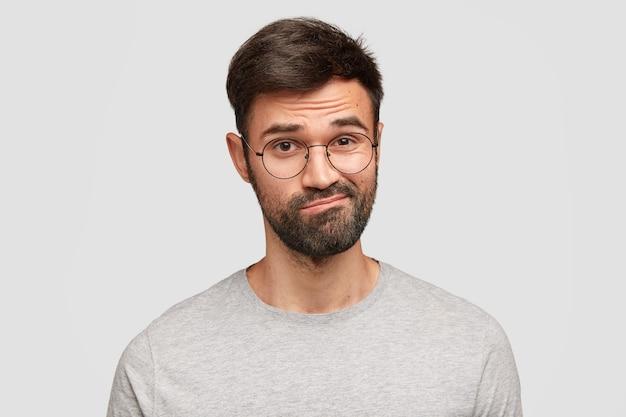 El hombre sin afeitar desconcertado y dudoso curva los labios, frunce el ceño con vacilación, tiene una expresión despistada