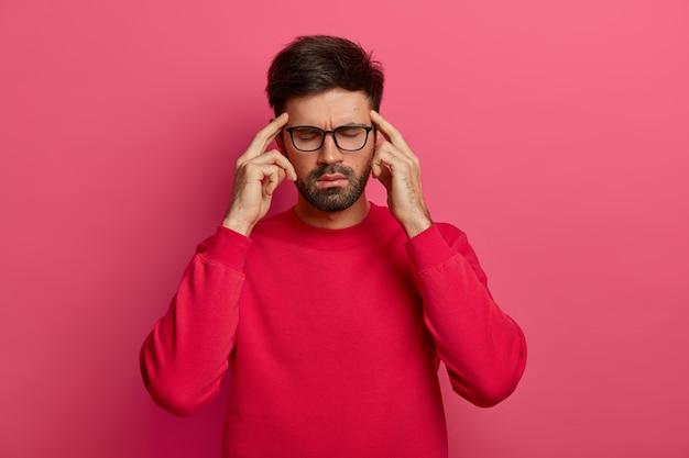 Hombre sin afeitar estresado cierra los ojos, mantiene los dedos índices en las sienes
