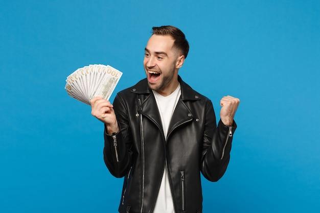 Hombre sin afeitar joven en camiseta blanca chaqueta de cuero negro con ventilador de dinero en efectivo en billetes de dólar aislado en retrato de estudio de fondo de pared azul. concepto de estilo de vida de personas. simulacros de espacio de copia.