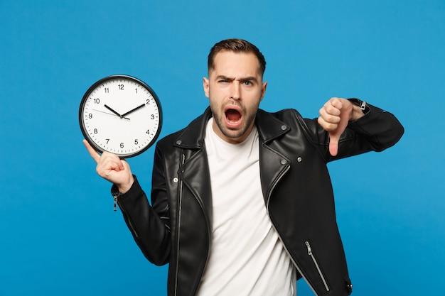 Hombre sin afeitar joven elegante molesto triste en camiseta blanca de la chaqueta de cuero negra que sostiene el reloj redondo aislado en retrato azul del estudio del fondo de la pared. concepto de estilo de vida de personas. darse prisa. simulacros de espacio de copia.