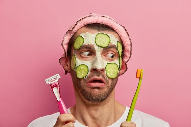 Hombre sin afeitar sorprendido mira con expresión de sorpresa en la maquinilla de afeitar y el cepillo de dientes