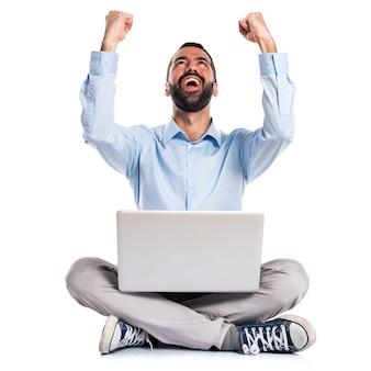 Hombre afortunado con la computadora portátil
