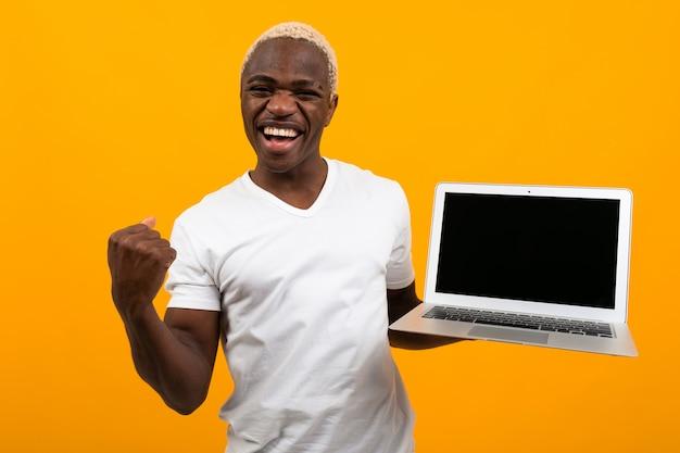 Hombre africano alegre agitando sus manos sosteniendo una computadora portátil con una maqueta sobre un fondo amarillo