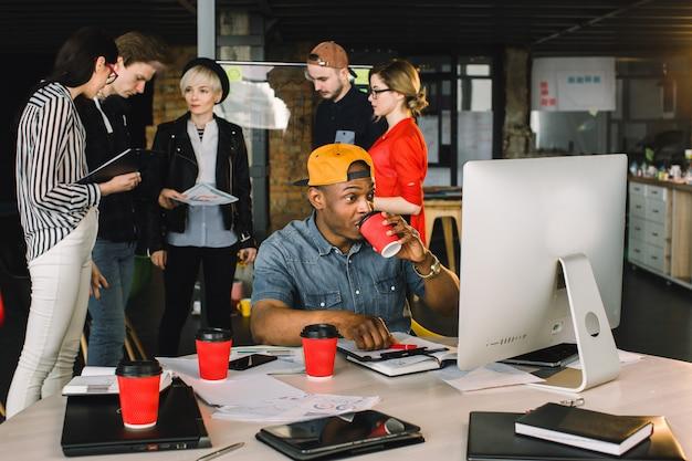 Hombre africano alegre bebiendo café y trabajando en la computadora mientras está sentado en la mesa en el lugar de la oficina moderna.
