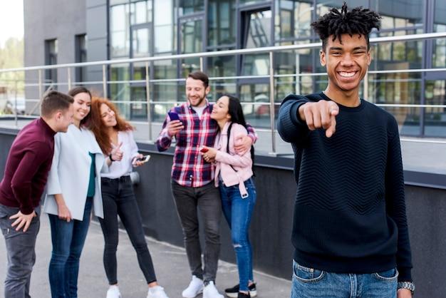 Hombre africano alegre que señala hacia la cámara de pie delante de sus amigos