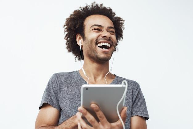 Hombre africano en auriculares riendo con tableta hablando o mirando y disfrutando de un espectáculo de comedia o navegación.
