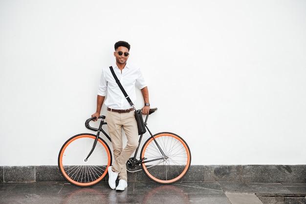 Hombre africano con bicicleta de pie en la pared blanca