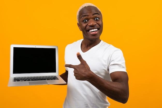 Hombre africano con cabello blanco sonriendo sosteniendo la pantalla del portátil hacia adelante con diseño apuntando a la pantalla sobre fondo amarillo