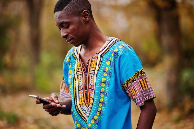 Hombre africano en camisa tradicional de áfrica en el parque de otoño.