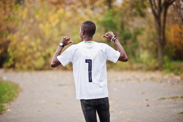 Hombre africano en camiseta deportiva de fútbol blanco del país de ghana áfrica con 7 números.