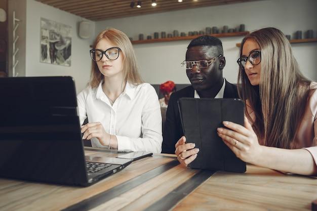 Hombre africano. chico de traje negro. estudiantes con laptop. chica de blusa blanca.