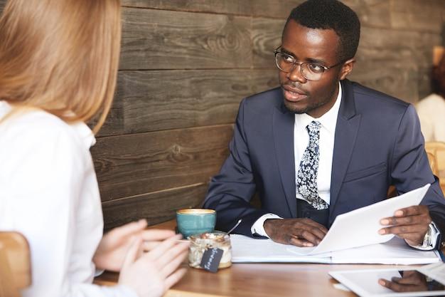 Hombre africano confiado en ropa formal con cv, escuchando atentamente a la mujer pelirroja
