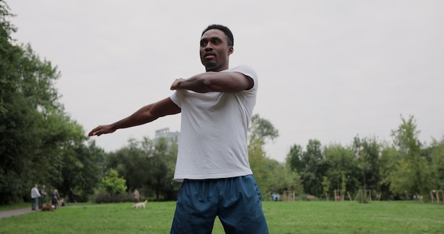 Hombre africano deportivo con calentamiento estirando los brazos antes de correr en el parque de la ciudad. deportista haciendo ejercicio al aire libre. concepto de estilo de vida saludable.
