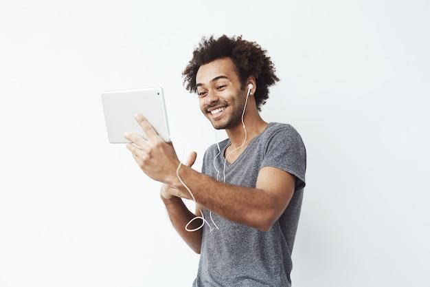 Hombre africano divertido en auriculares riendo mirando tableta.