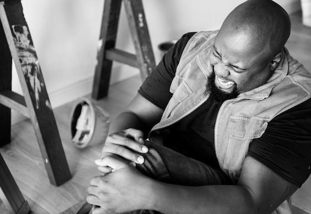 Hombre africano con dolor en las piernas