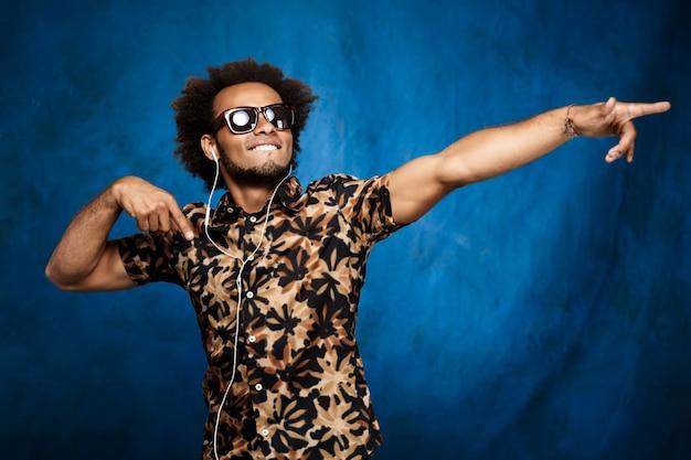 Hombre africano escuchando música en auriculares, bailando sobre la pared azul.
