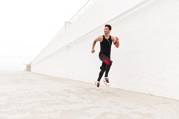 Hombre africano feliz deportes corriendo al aire libre.
