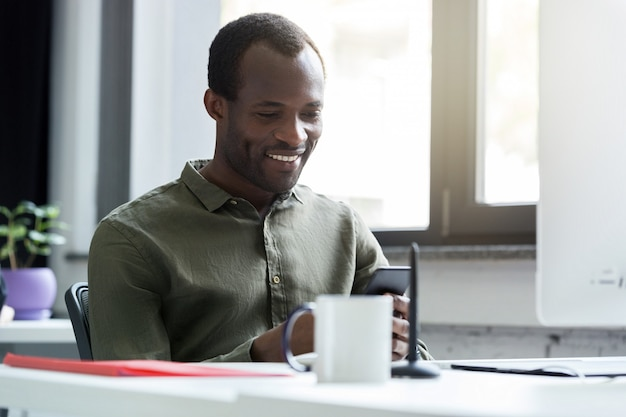 Hombre africano feliz mirando su teléfono móvil