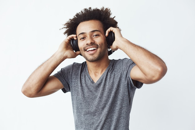 Hombre africano feliz sonriendo escuchando música en auriculares.