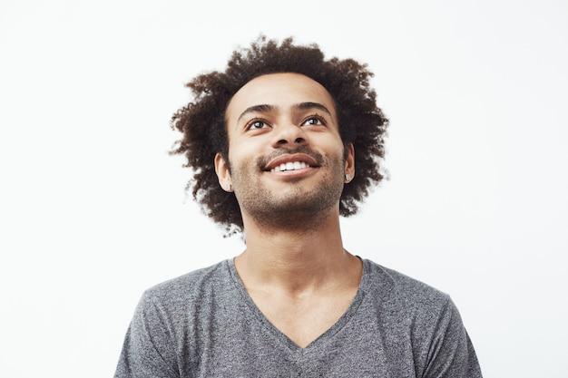 Hombre africano feliz sonriendo mirando hacia arriba.