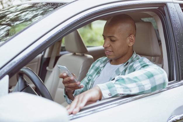 Hombre africano guapo disfrutando de viajar en coche en un viaje por carretera
