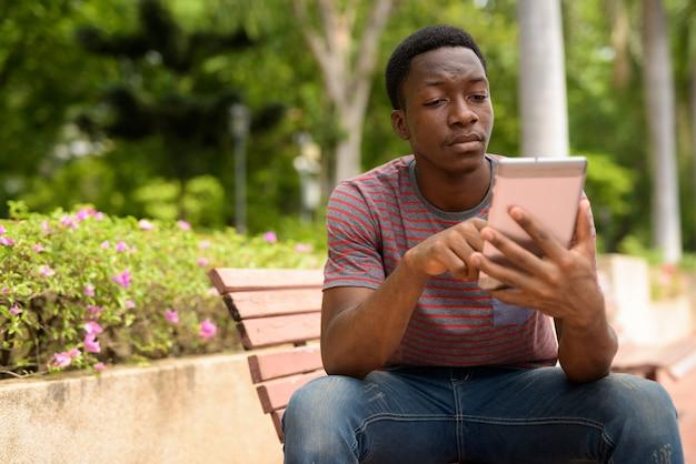 Hombre africano guapo joven con tableta digital en el parque