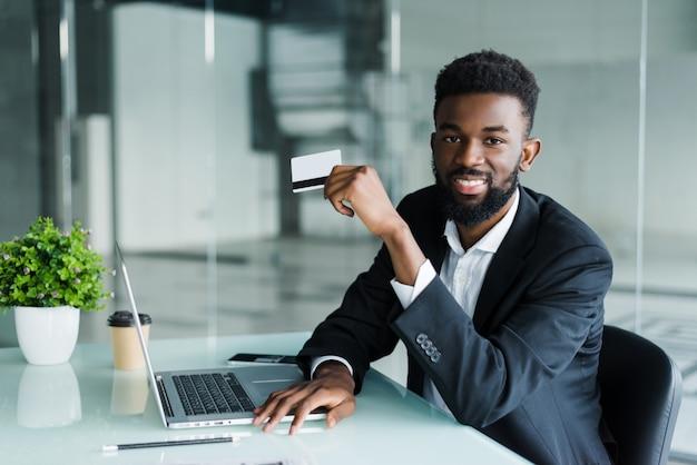 Hombre africano hablando por teléfono y leyendo el número de tarjeta de crédito mientras está sentado en la oficina