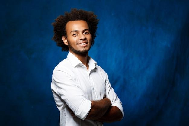 Hombre africano hermoso joven con los brazos cruzados sobre la pared azul.
