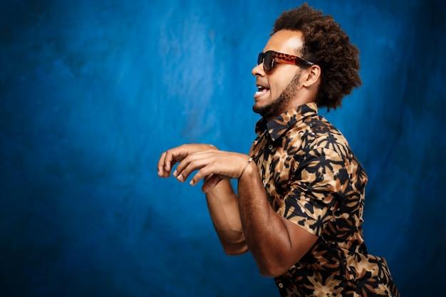 Hombre africano hermoso joven en gafas de sol que engaña sobre la pared azul.