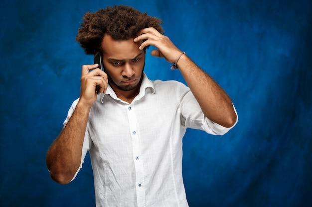 Hombre africano hermoso joven que habla en el teléfono sobre la pared azul.