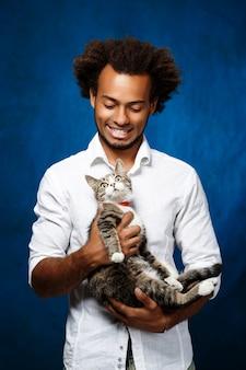 Hombre africano hermoso joven que sostiene el gato sobre la pared azul.