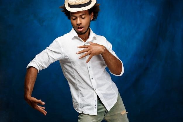 Hombre africano hermoso joven en el sombrero que baila sobre la pared azul.
