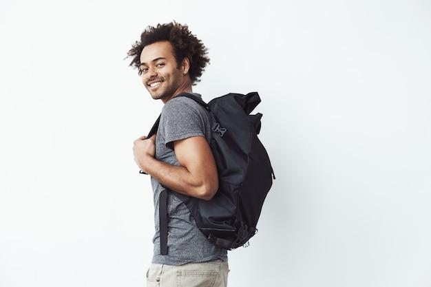 Hombre africano hermoso con la mochila que sonríe de pie contra la pared blanca lista para ir de excursión o un estudiante en su camino a la universidad