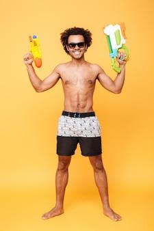 Hombre africano joven alegre que sostiene la pistola de agua del juguete.