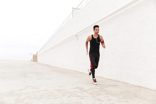 Hombre africano joven deportes corriendo al aire libre.