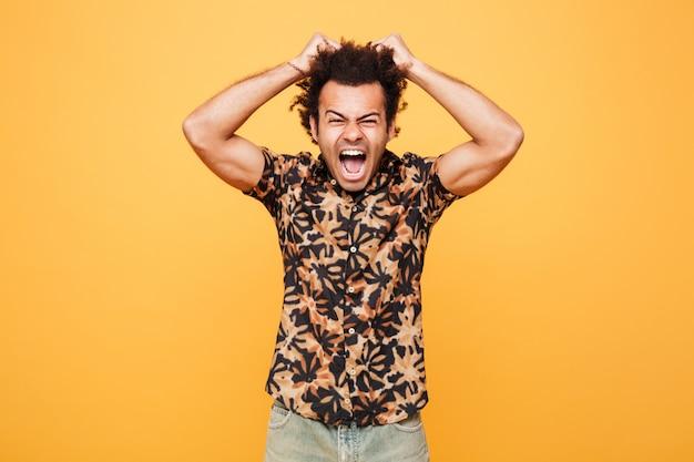 Hombre africano joven enojado gritando de pie sobre la pared amarilla.