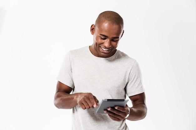 Hombre africano joven feliz que usa la tableta.