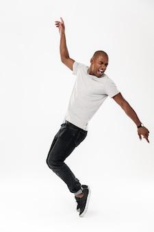 Hombre africano joven gritando emocional bailando aislado