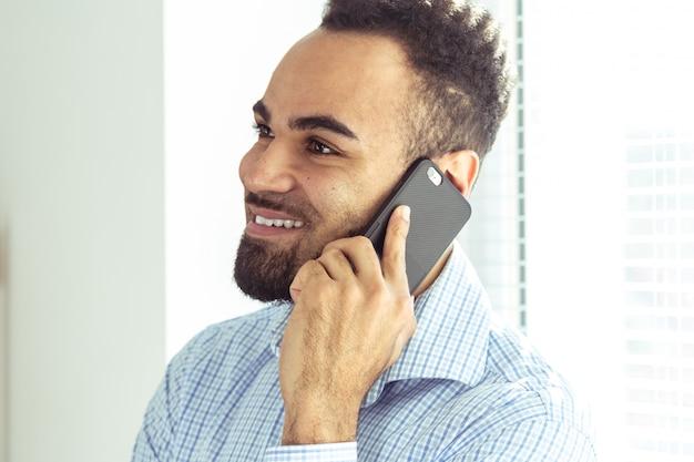 Hombre africano joven hermoso que sostiene el teléfono elegante