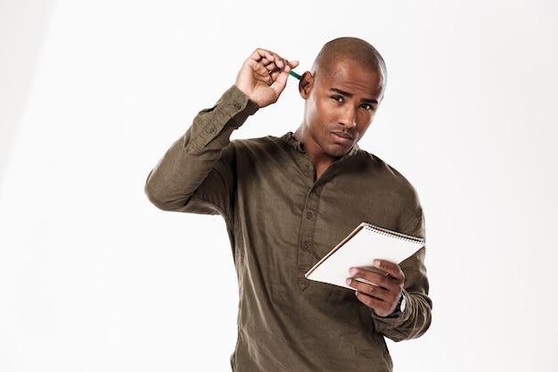 Hombre africano joven pensativo escribiendo notas mirando.