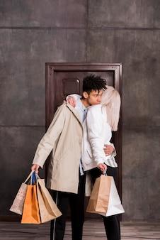 Hombre africano joven que abraza a su novia que sostiene muchos bolsos de compras disponibles