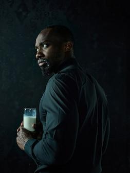 Hombre africano joven sano que sostiene la taza de leche sobre un fondo negro del estudio.