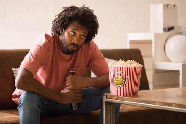Hombre africano joven viendo la televisión, se aburre, sosteniendo un cubo de palomitas de maíz.