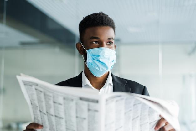 Hombre africano leyó los últimos periódicos con una máscara sobre la situación en el mundo en la oficina