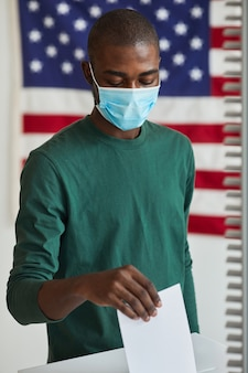 Hombre africano en máscara protectora poniendo la papeleta en la urna que vota durante la pandemia
