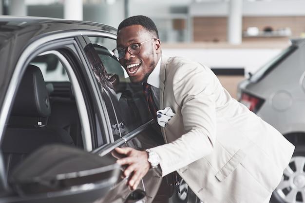 Hombre africano mirando un coche nuevo en el concesionario de coches.