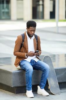 Hombre africano moderno con smartphone en la ciudad